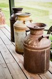 Three Old Milk Cans. Three Antique Milk Cans sitting on an Old Porch Royalty Free Stock Photos