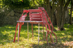 Three old, red folding chairs Stock Photo