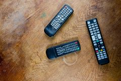 Three old remote controls from televisions and videos on destroyed table surface stock photo