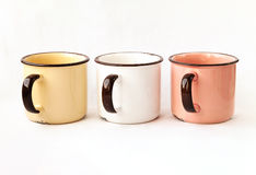 Three old retro metal tea cups in a row isolated. Some yellow, white, rose pastel color beautiful ceramic mugs for coffee royalty free stock image
