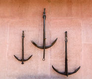 Three old rusty anchor hanging on the plastered wall burgundy Stock Photos