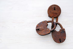 Three old rusty door padlocks on wooden background. Three old rusty door padlocks on wooden white background Royalty Free Stock Images