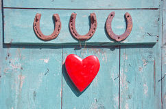 Three old rusty horseshoe luck symbol and red heart on door Royalty Free Stock Photos