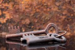 Three old rusty keys with reflections Stock Photos