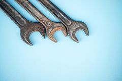 Three old rusty spanners on blue background. Workshop equipment. royalty free stock image