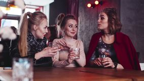Three old sexy friends having a trustful conversation in the bar, holding glasses of alcohol cocktails. Fashionable look stock video