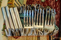 Three old silver forks and four knives on the table covered by colorful rug stock images