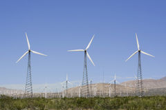Three Old Style Wind Turbines. Three 1st generaltion steel trussed wind turbines stand in front of hundreds of turbines at the San Gorgonio Pass wind farm near Stock Photo