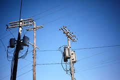 Three old utility poles against clear blue sky stock images