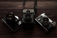 Three old vintage cameras on a wooden table. Royalty Free Stock Photo
