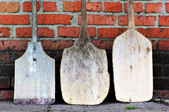 Three old vintage spades. Leaning against red brick wall Royalty Free Stock Photos