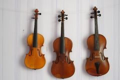 Three old violins of hanging on the wall royalty free stock photography
