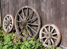 Three old wagon wheels. With metal rims leaning against a wall of wooden planks Stock Photo