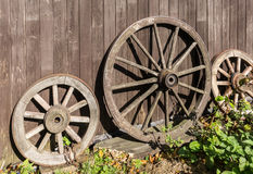 Three old wagon wheels. With metal rims leaning against a wall of wooden planks Stock Image