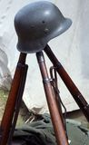 Three old war rifles and helmets of dead soldier at war Stock Photos