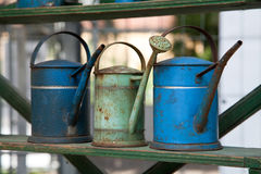 Three old watering pots outdoors Royalty Free Stock Photo