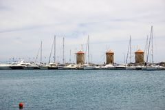 Three old windmills standing near blue Mediterranean sea royalty free stock photo