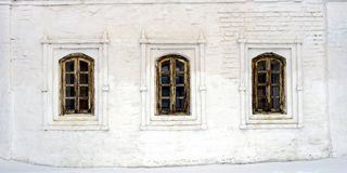 Three old Windows in wooden frames in a stone white wall royalty free stock image
