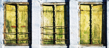 Three old windows with wooden shutters Stock Images