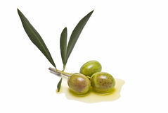 Three olives on olive oil Stock Photos