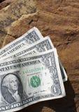 Three One Dollar Bills. A group of one dollar bills sit on a rock Royalty Free Stock Photos