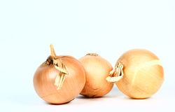 Three Onions. Three yellow onions on a light background Royalty Free Stock Photos