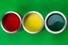 Three open cans of paint on a green background royalty free stock photos