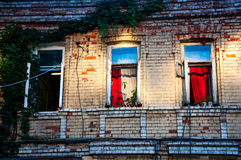 Three open windows on brick building in the evening Stock Image