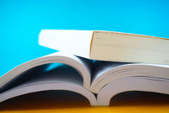 Three opened books in blue background. In the image, there are two opened books. They are on a wooden table and they are in the blue background stock image