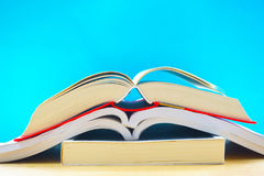 Three opened books in blue background. In the image, there are two opened books. They are on a wooden table and they are in the blue background royalty free stock photo