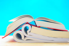 Three opened books in blue background. In the image, there are two opened books. They are on a wooden table and they are in the blue background royalty free stock images