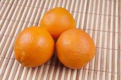 Three orange. On bamboo background Royalty Free Stock Photo