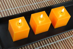 Three orange candles in black dish. On bamboo Royalty Free Stock Image