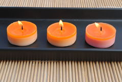 Three orange candles in black dish on bamboo. Orange candles in black dish on bamboo Stock Images