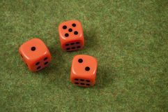Three orange dice. Over a red and green carpet Stock Photo