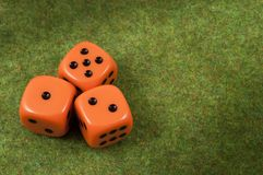 Three orange dice togheter. Three orange dice over a red and green carpet Royalty Free Stock Images
