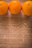 Three orange fruits on wooden table with organized Stock Photography