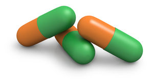 Three orange and green capsules close up Stock Images