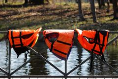 Three orange lifejackets hang on the railing near the pier at the boat station. Gatchina, Russia. Three orange lifejackets hang on the railing near the pier at royalty free stock photo