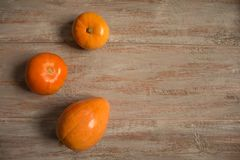 Three orange pumkins on the wooden boards. stock photos
