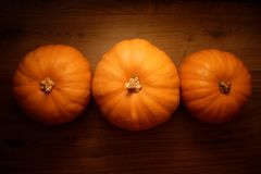 Three orange pumpkins on a wooden background. royalty free stock photos