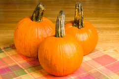 Three orange pumpkins on a wooden table Royalty Free Stock Photography