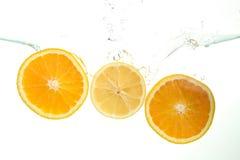 Three orange slices splash of water on white stock photography
