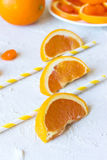 Three orange slices on a textural background. Three orange slices on a textural light gray background Royalty Free Stock Images