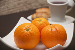 Three oranges. Whole oranges, with tea and croissants in background Royalty Free Stock Photos