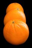 Three oranges arranged on black Royalty Free Stock Images