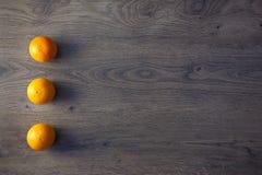 Three Oranges are on empty dark Wooden Table Stock Photo