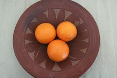 Three oranges inside a ceramic plate stock images