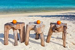 Three oranges are on original  beach tables Royalty Free Stock Photography