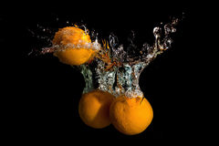 Three oranges in water raised a big wave Royalty Free Stock Photos